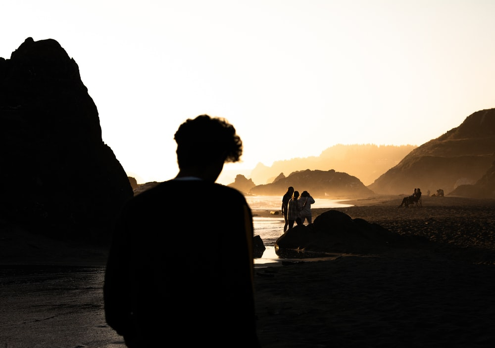 silhouette of man and woman sitting on rock near body of water during daytime