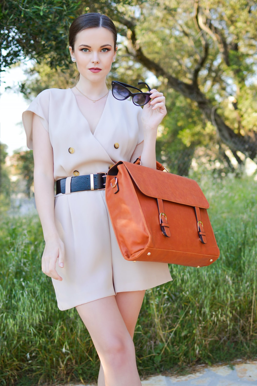 woman in brown dress with brown leather sling bag