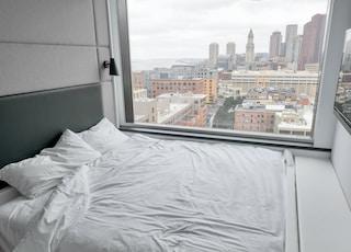 white bed linen near glass window