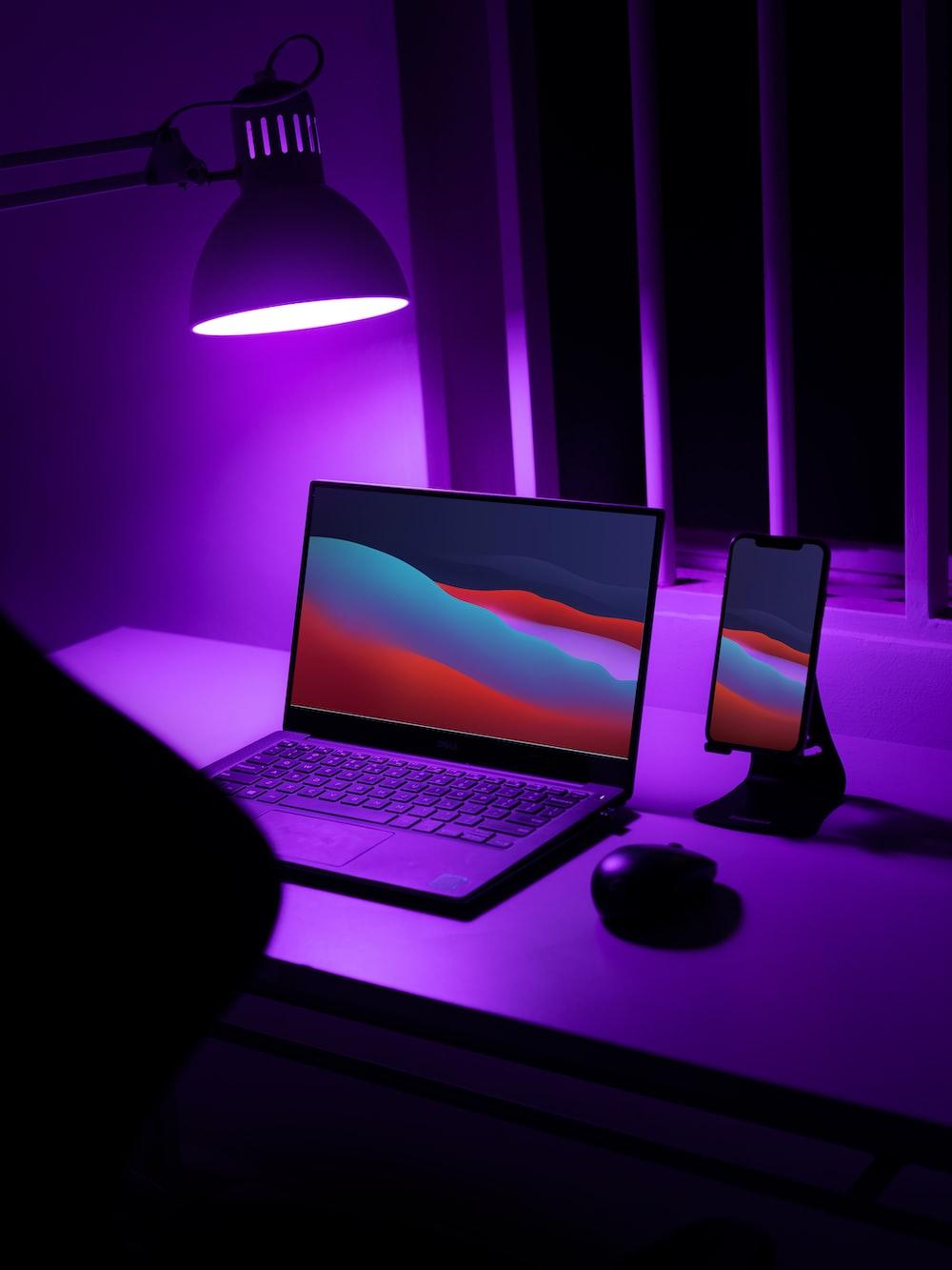 black laptop computer turned on beside black and silver desk lamp