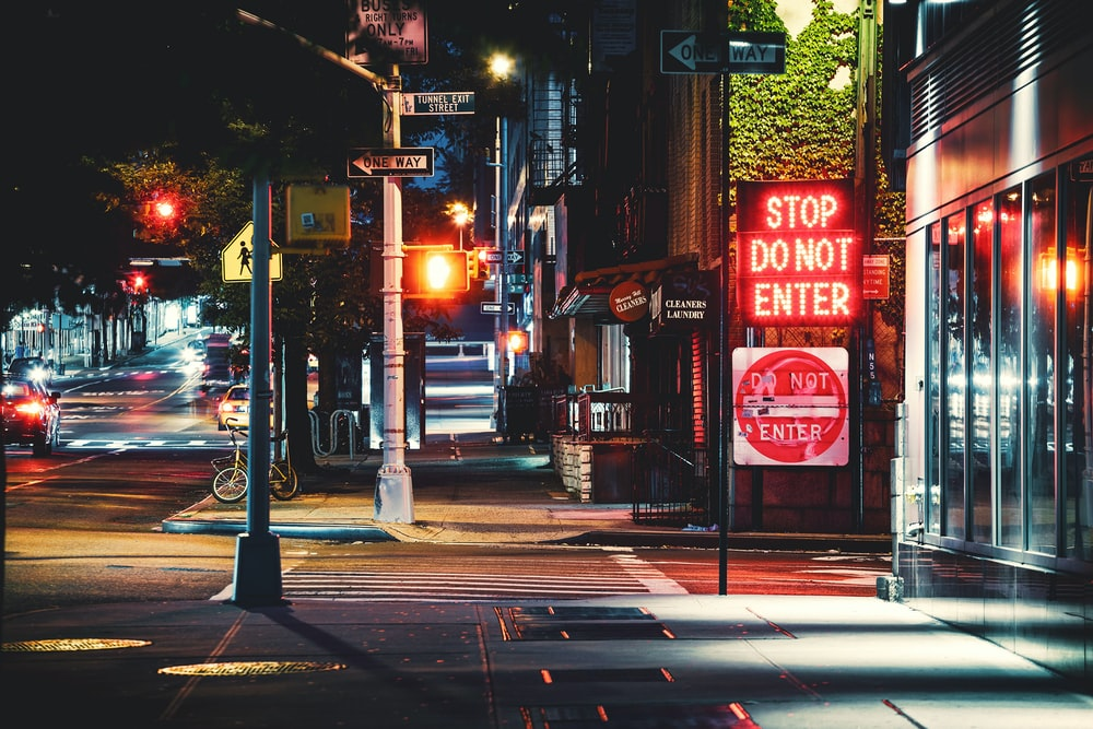 red and white stop light sign on sidewalk during night time