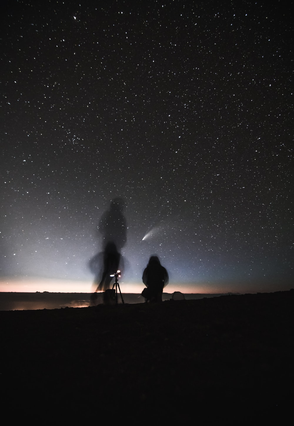 silhouette of 2 person standing on hill during night time