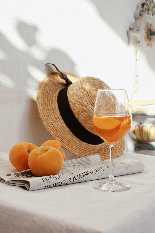 orange fruit on brown woven basket beside clear wine glass