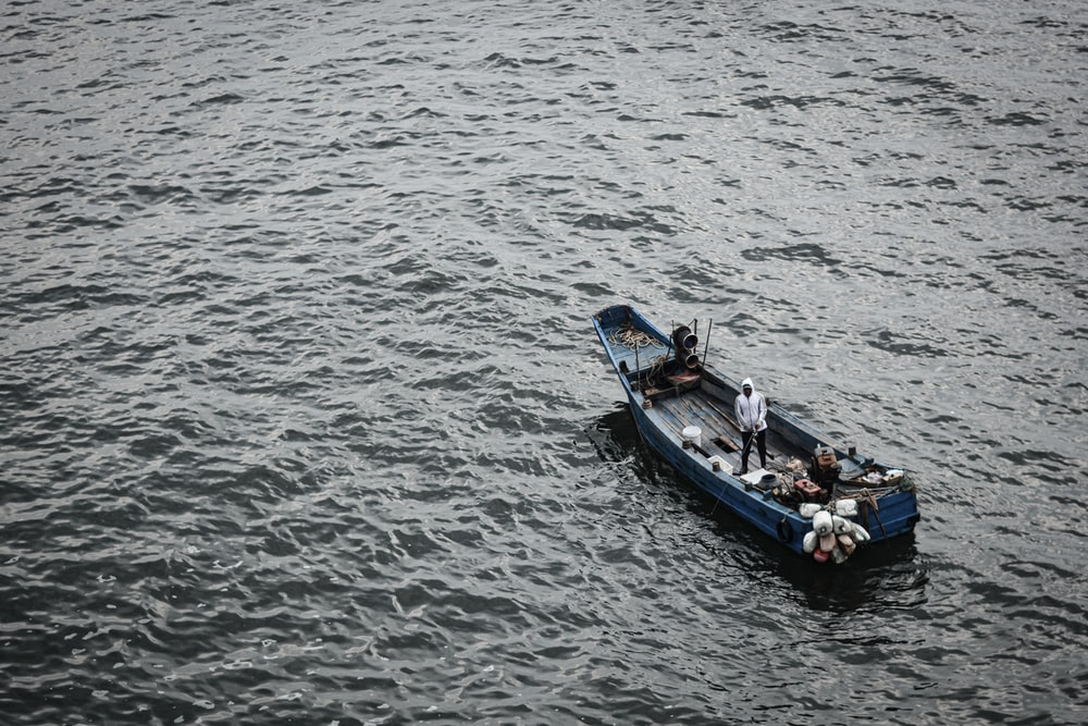 people riding on blue boat on sea during daytime