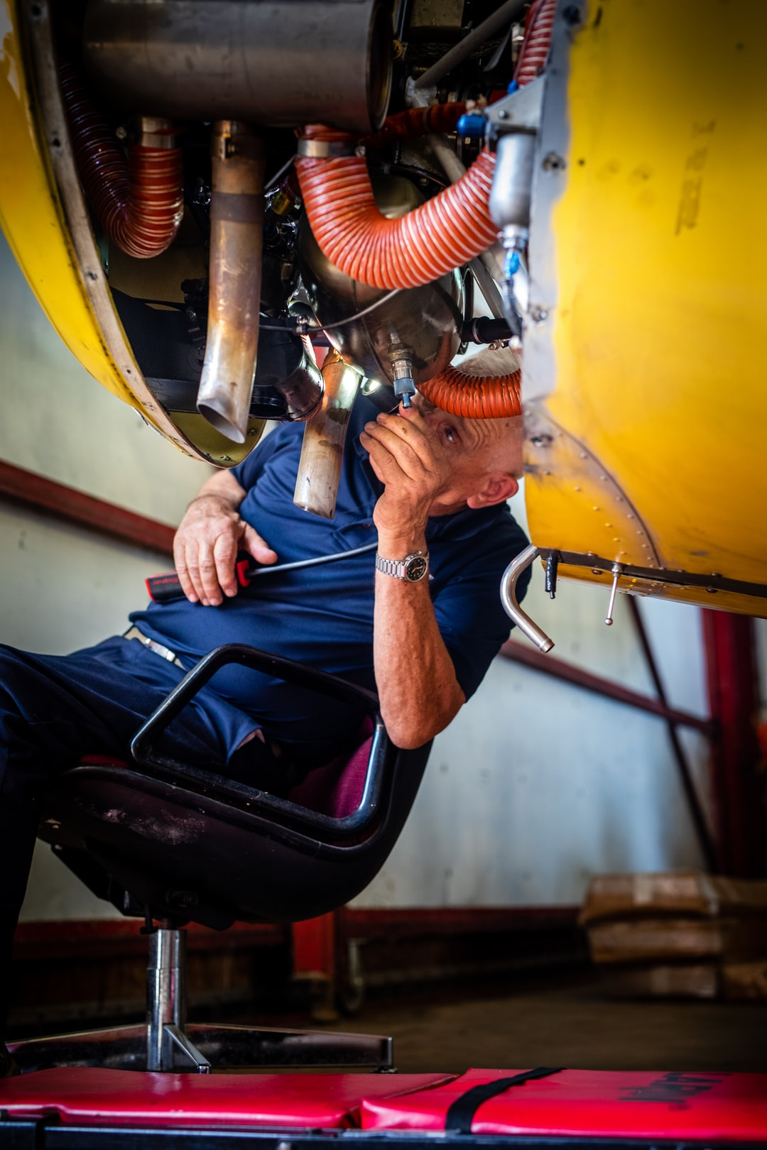 Older man doing maintenance on a plane