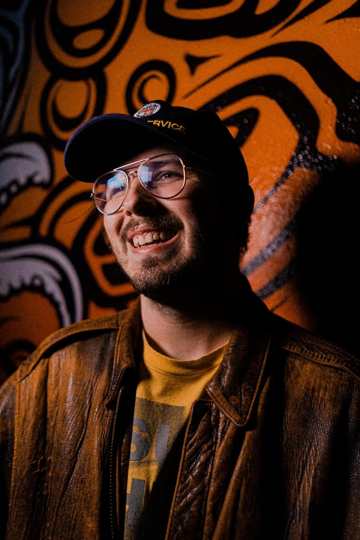 man in black cap and black framed eyeglasses