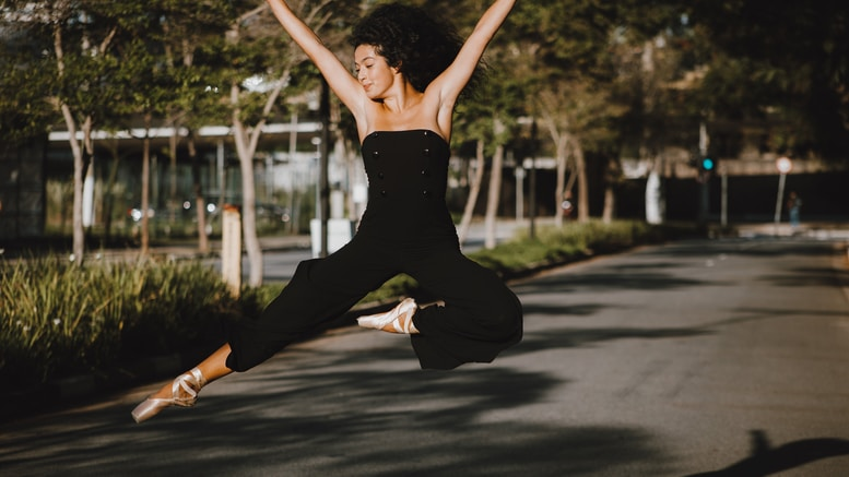 woman in black tank top and black pants doing yoga on gray asphalt road during daytime