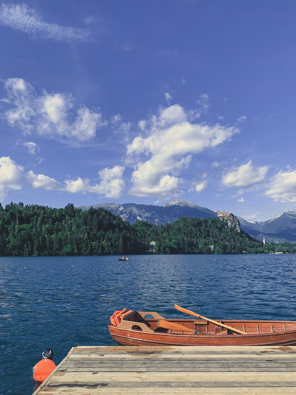 brown boat on body of water near green trees under blue sky during daytime