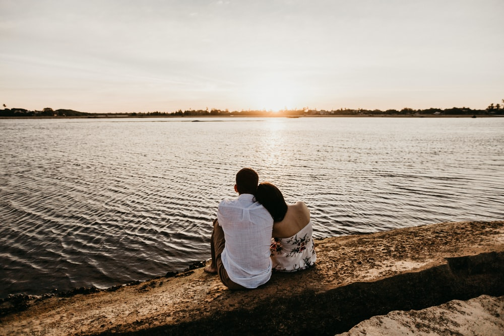 couple sitting on brown sand near body of water during daytime