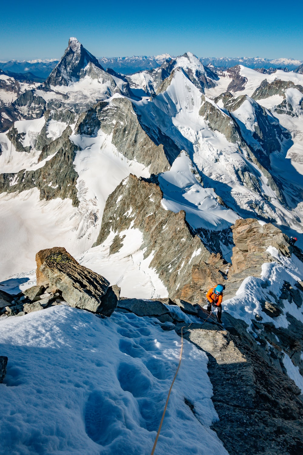 person in orange jacket and black pants standing on snow covered mountain during daytime