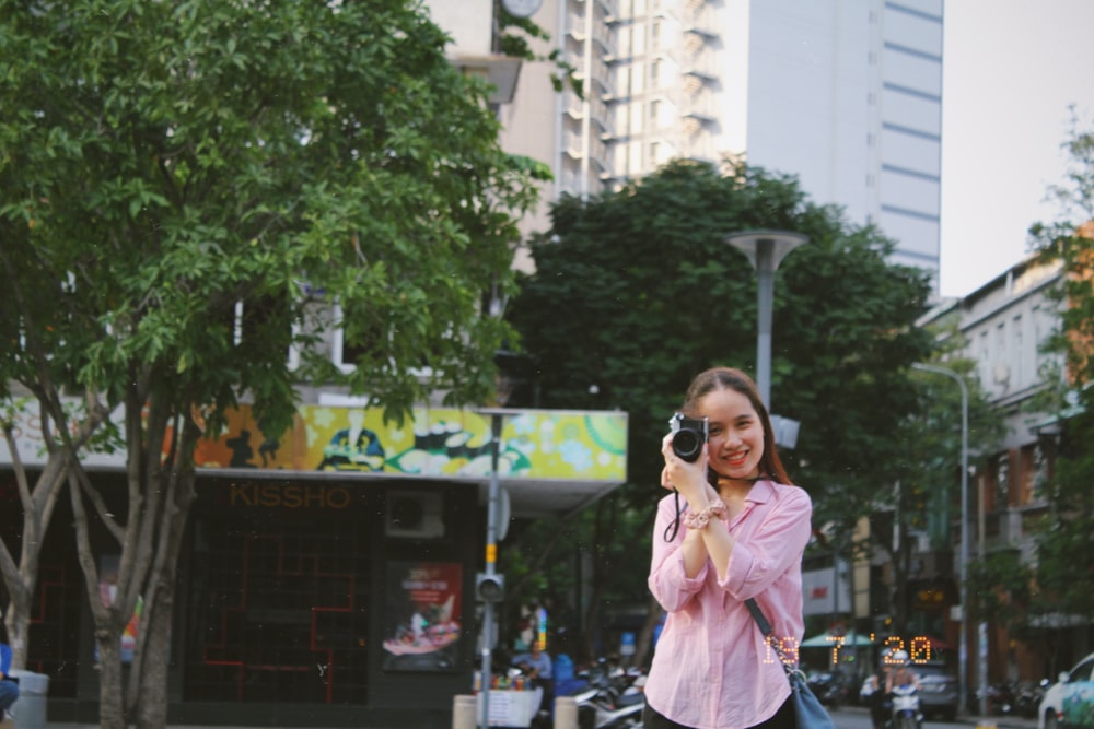 woman in pink coat holding black camera standing near green tree during daytime