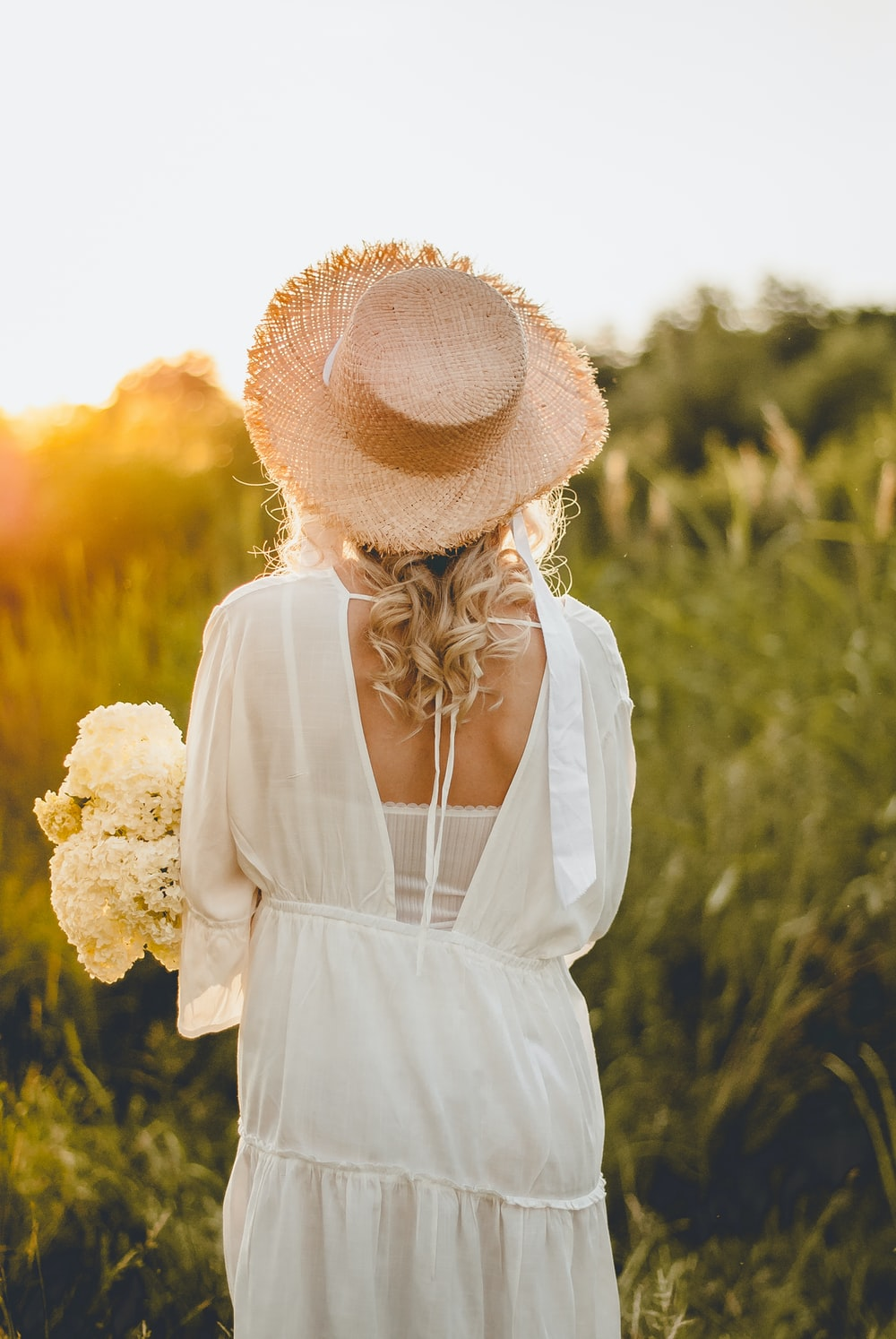 woman in white dress wearing brown sun hat standing on yellow flower field during daytime