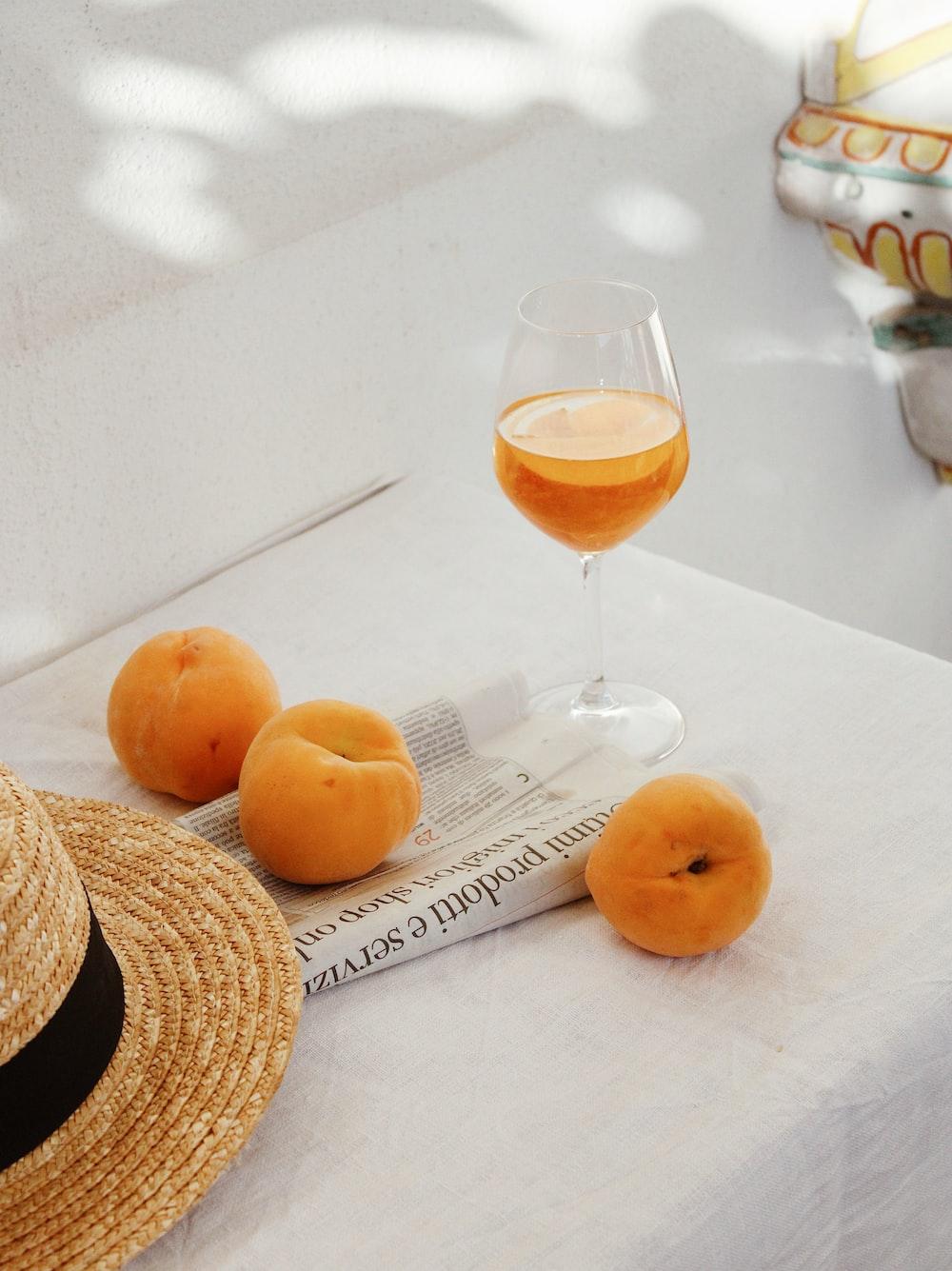 orange fruit beside clear wine glass