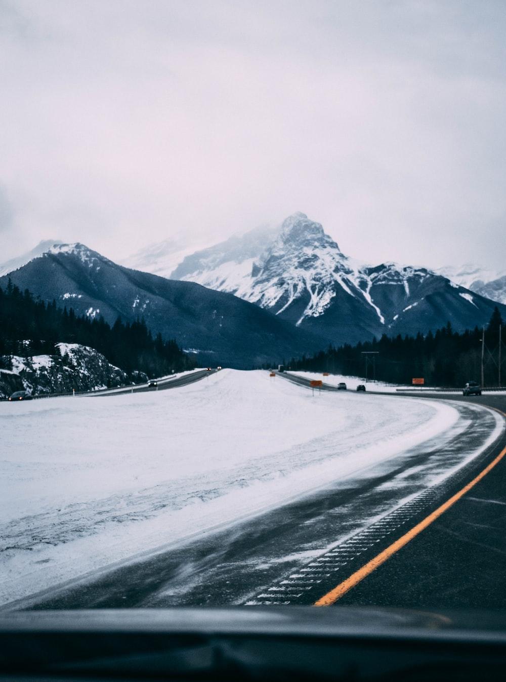 black asphalt road near snow covered mountain during daytime