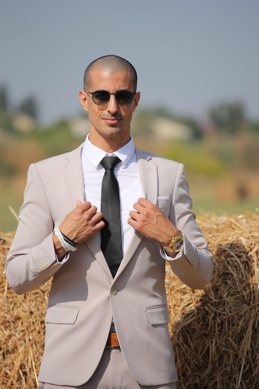 man in beige blazer wearing black sunglasses