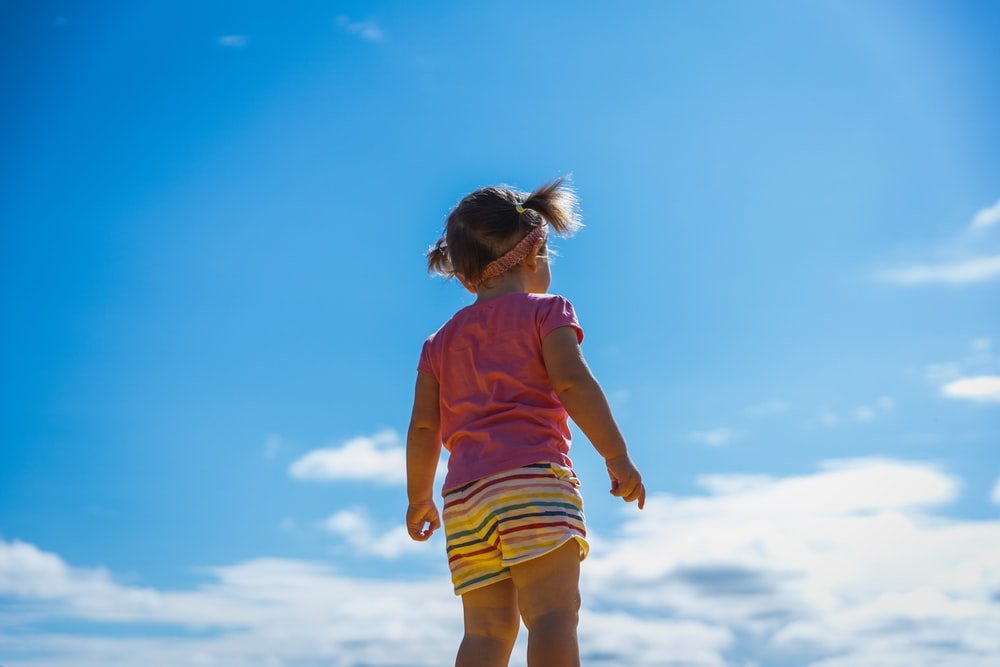 girl in pink t-shirt and yellow shorts standing on white clouds during daytime