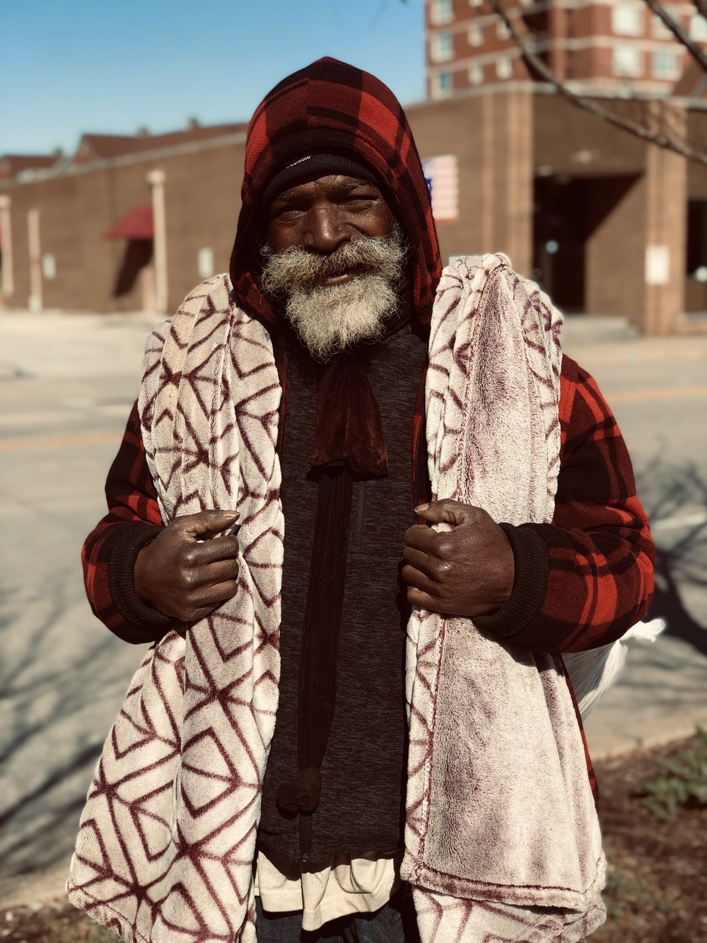 man in red and black coat standing during daytime