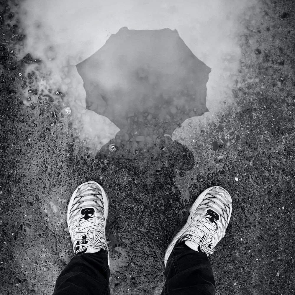 person in black pants and white sneakers standing on water
