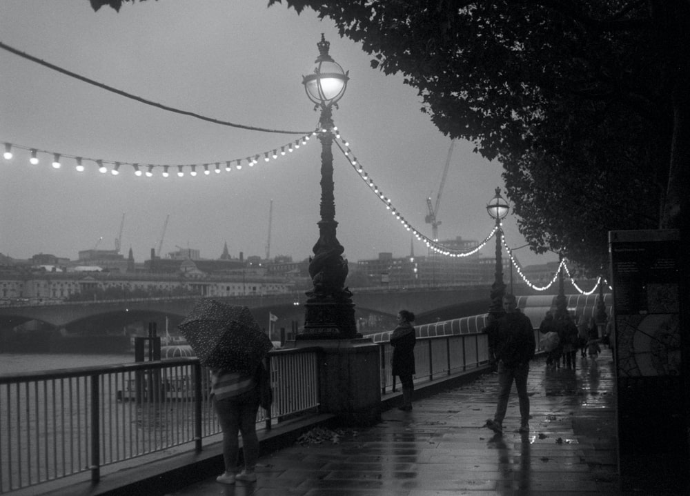grayscale photo of people walking on bridge