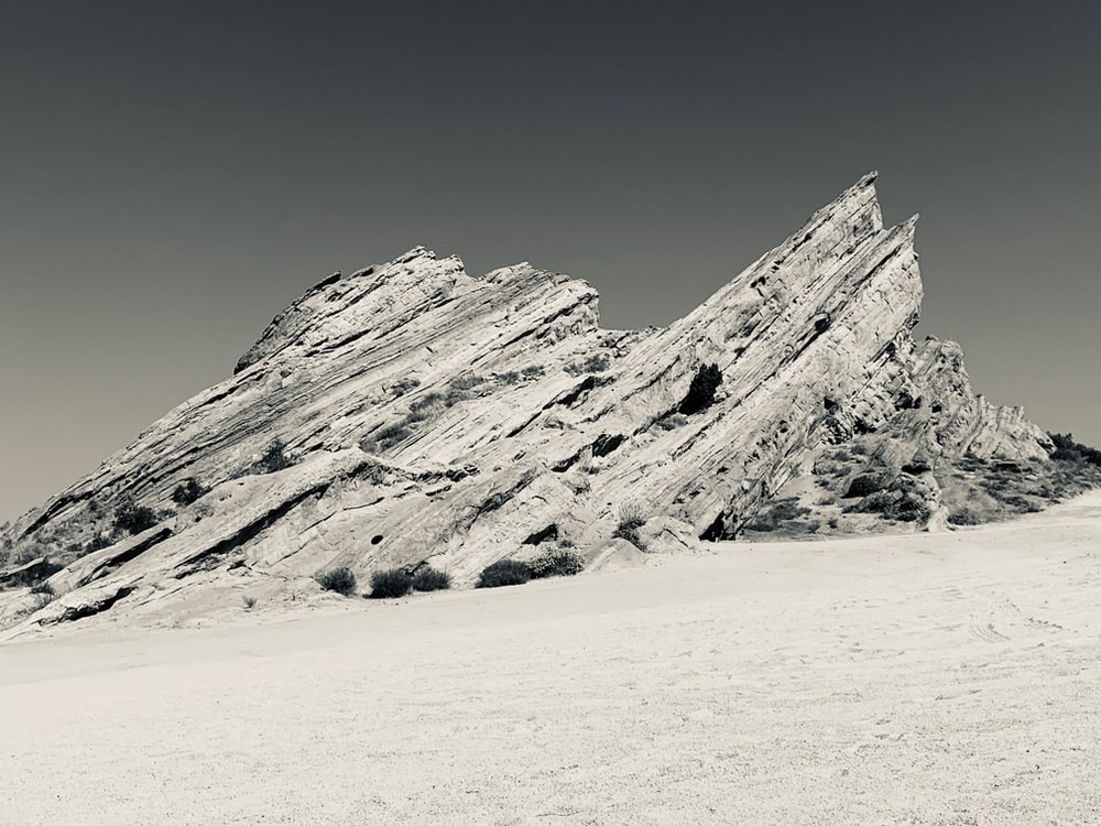 gray rock formation on white sand during daytime