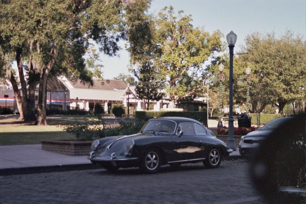 black sedan parked near green trees during daytime