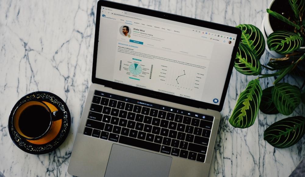 macbook pro beside white ceramic mug