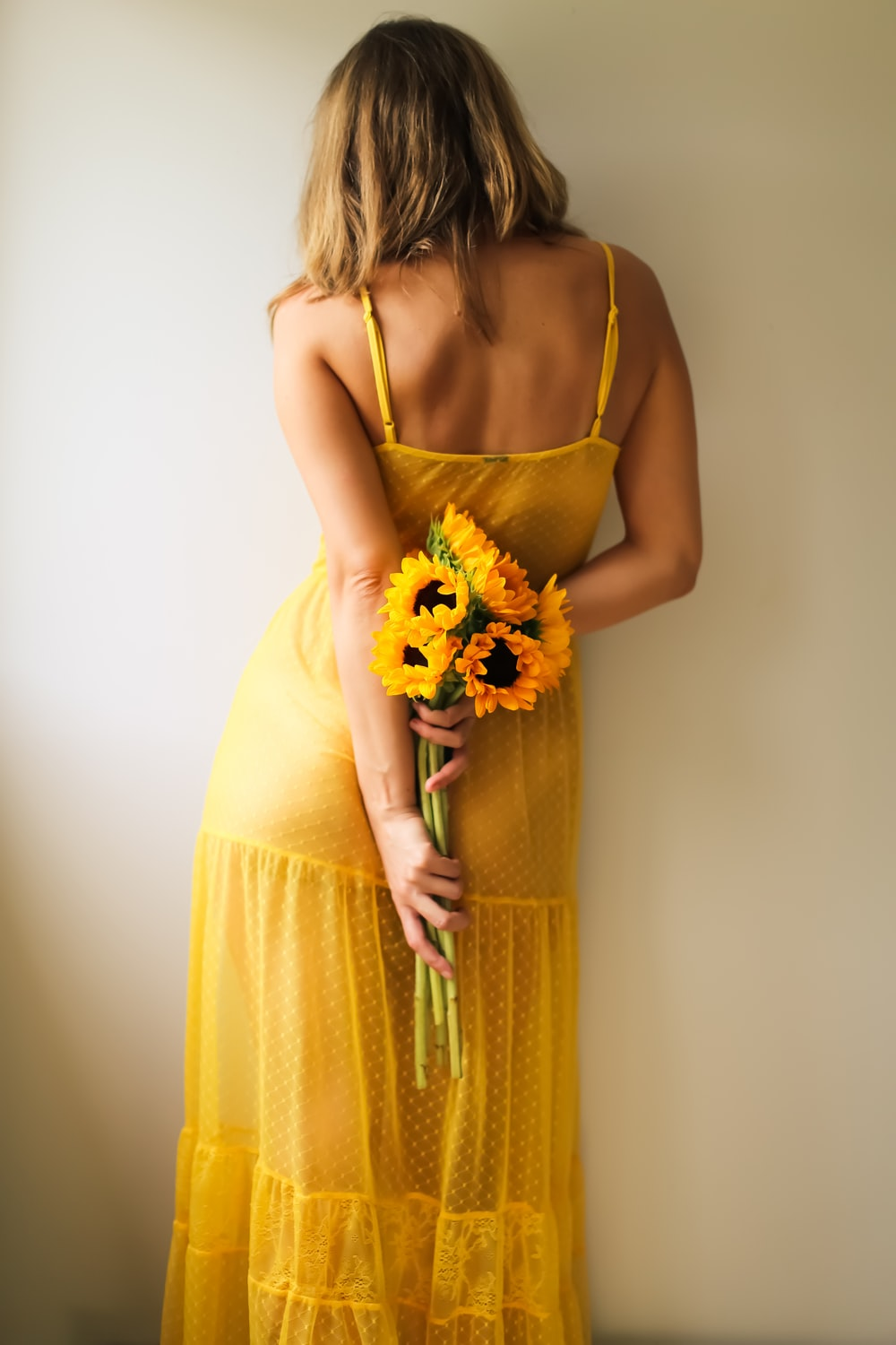 woman in yellow spaghetti strap dress holding yellow and white flower bouquet