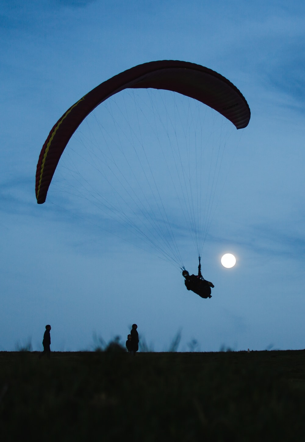 silhouette of people riding parachute during daytime