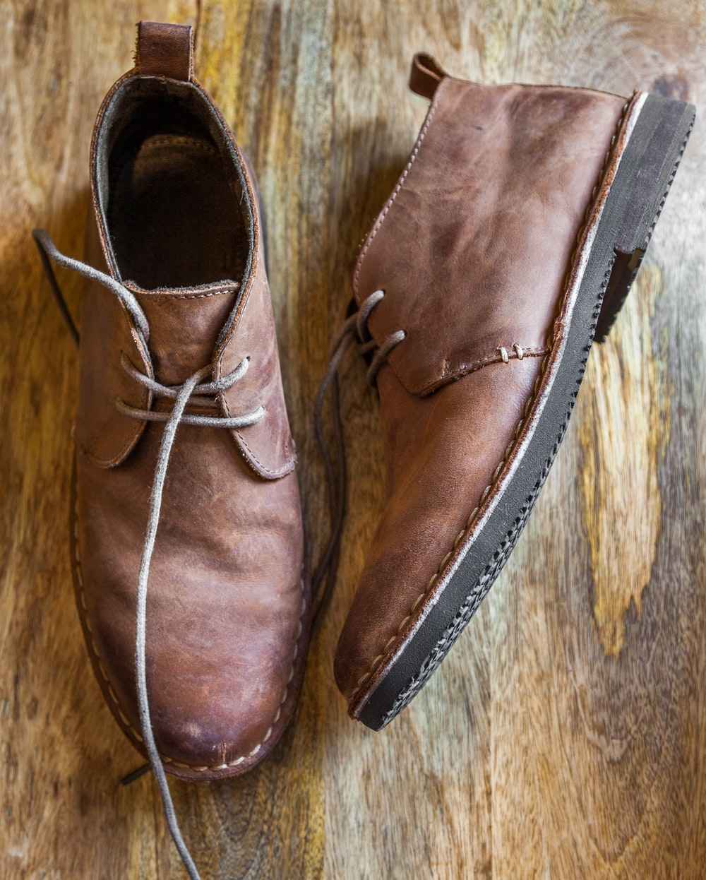 brown leather shoes on brown wooden surface
