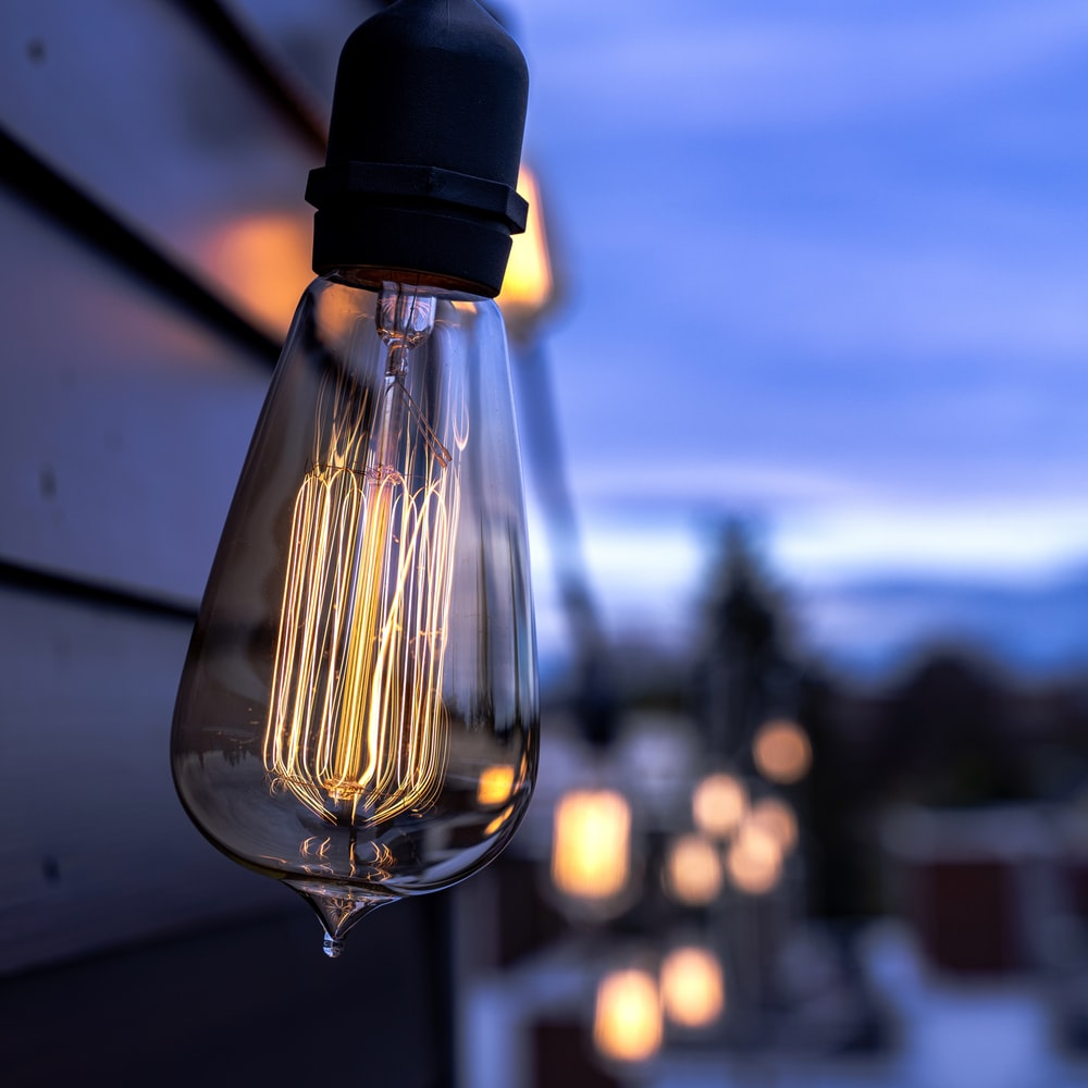 clear light bulb turned on during daytime