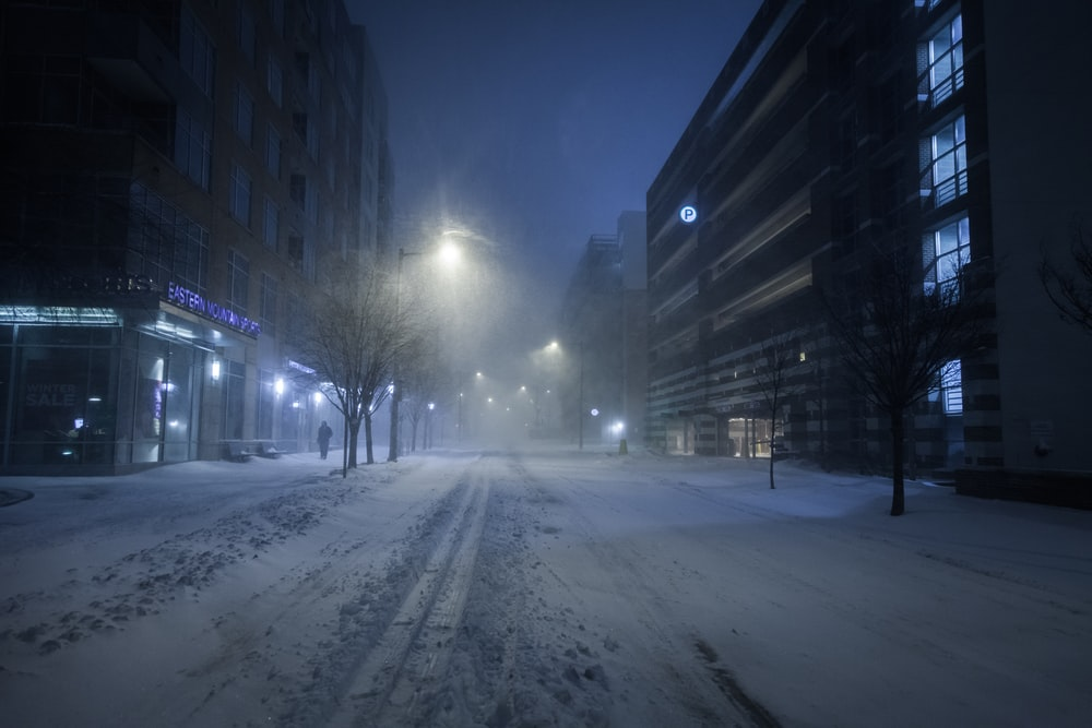 snow covered road between buildings during night time