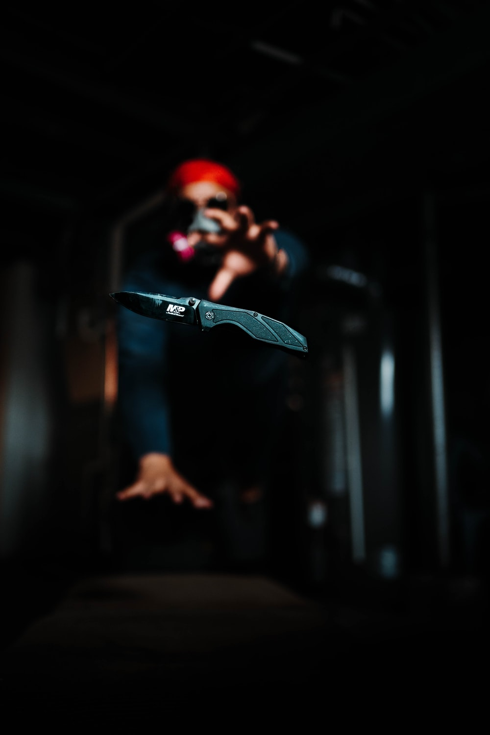 man in black and red mask holding black skateboard
