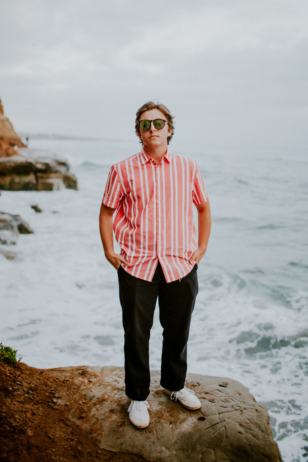 man in pink and white striped button up shirt standing on rock formation near sea during