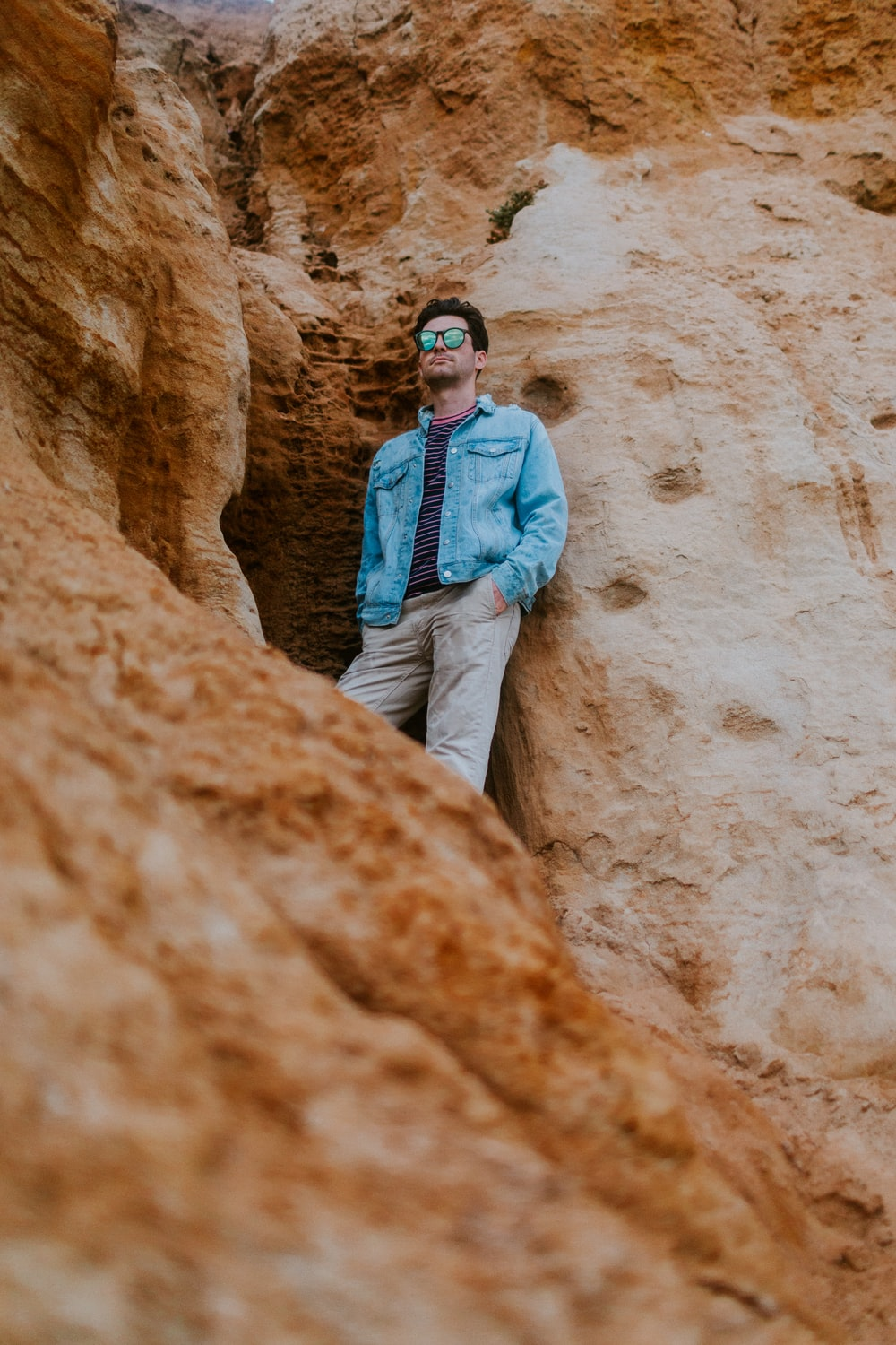 man in blue denim jacket and brown pants standing on brown rock formation during daytime