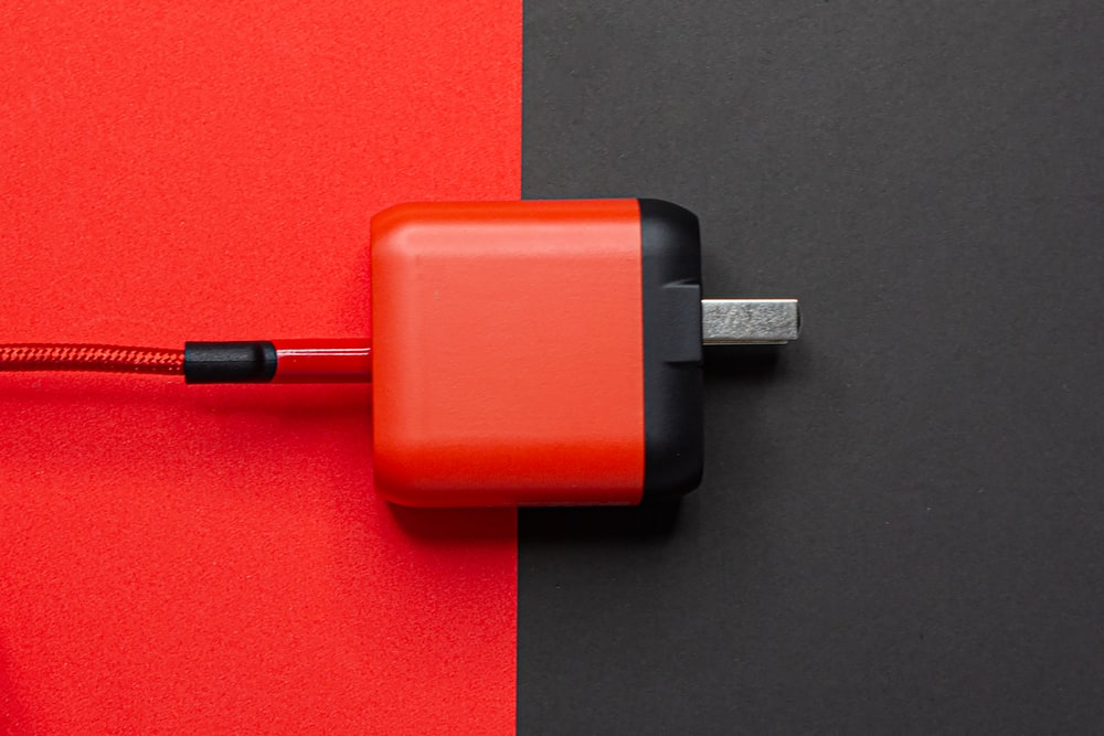 red and black adapter on red table