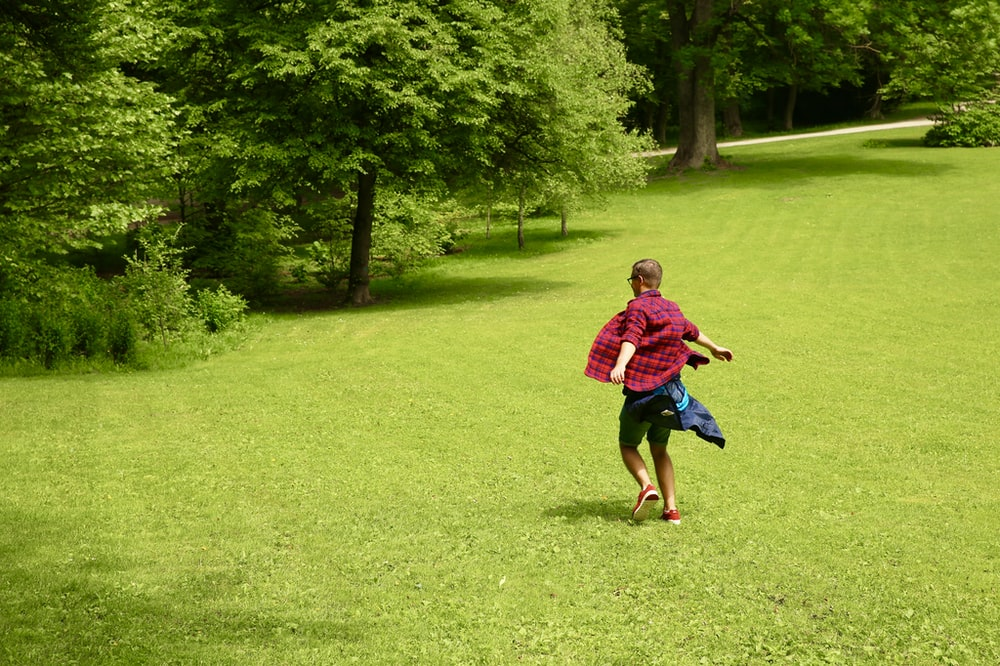 boy in red shirt running on green grass field during daytime