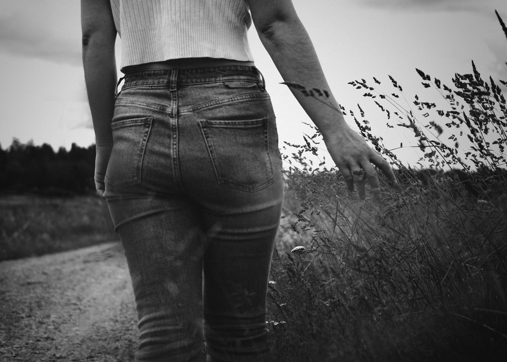 grayscale photo of woman in white tank top and black denim jeans