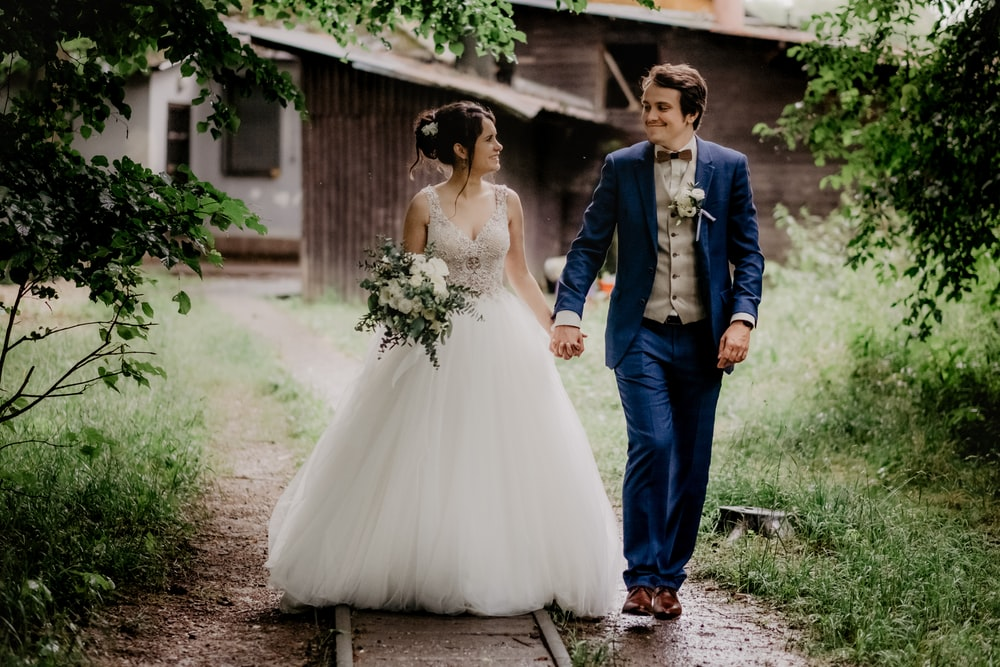 woman in white wedding gown beside man in blue suit