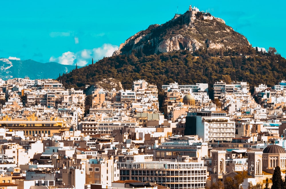 city buildings near mountain under blue sky during daytime