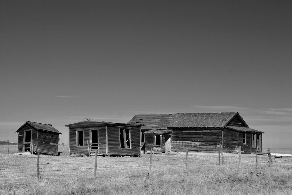 grayscale photo of wooden house on grass field
