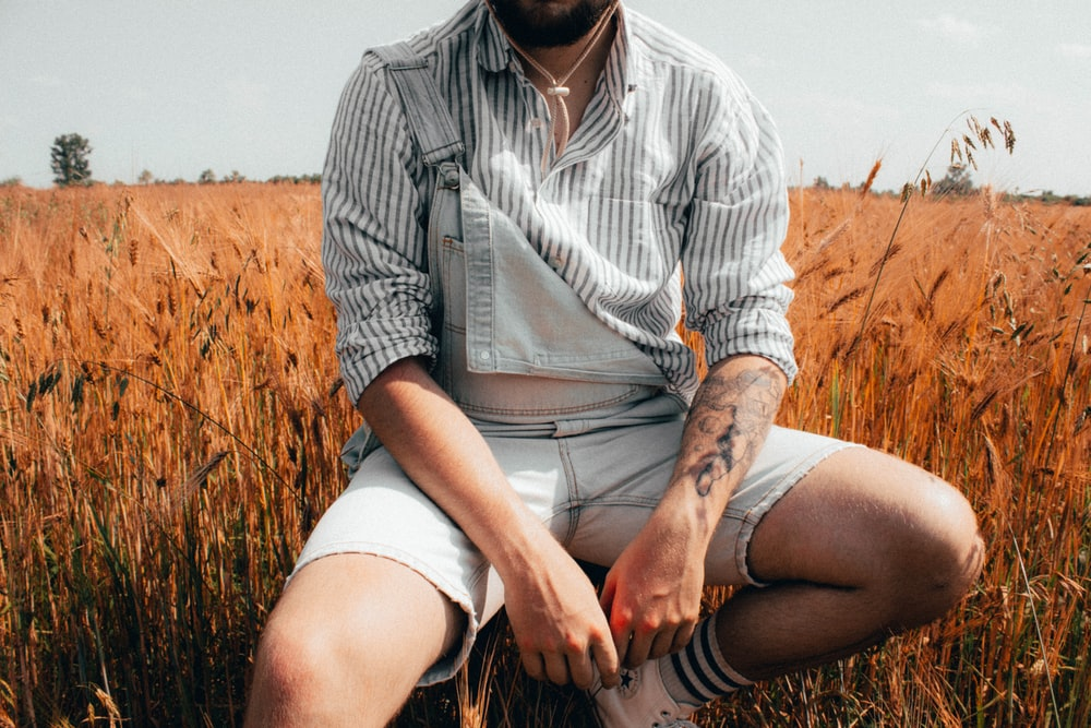 man in white and black stripe button up shirt sitting on brown grass field during daytime
