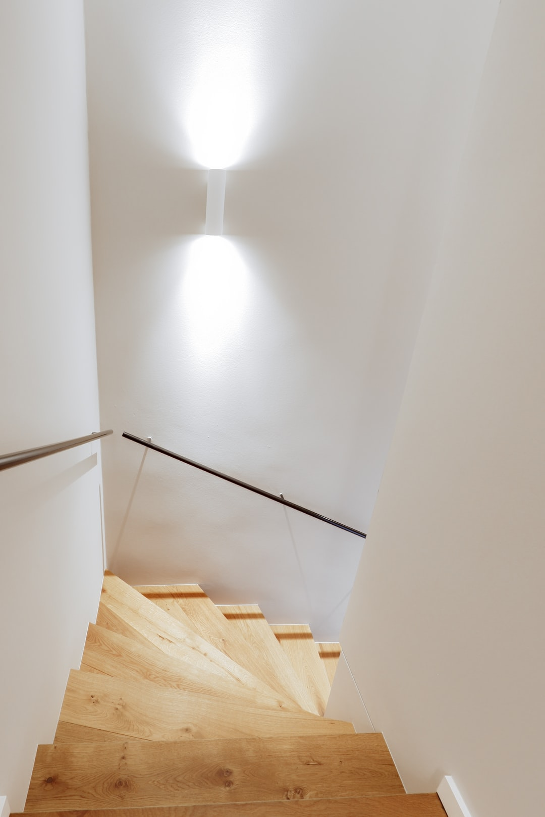Stairway in a remodeled  60s building. Oakwood stairs with an iron handrail.