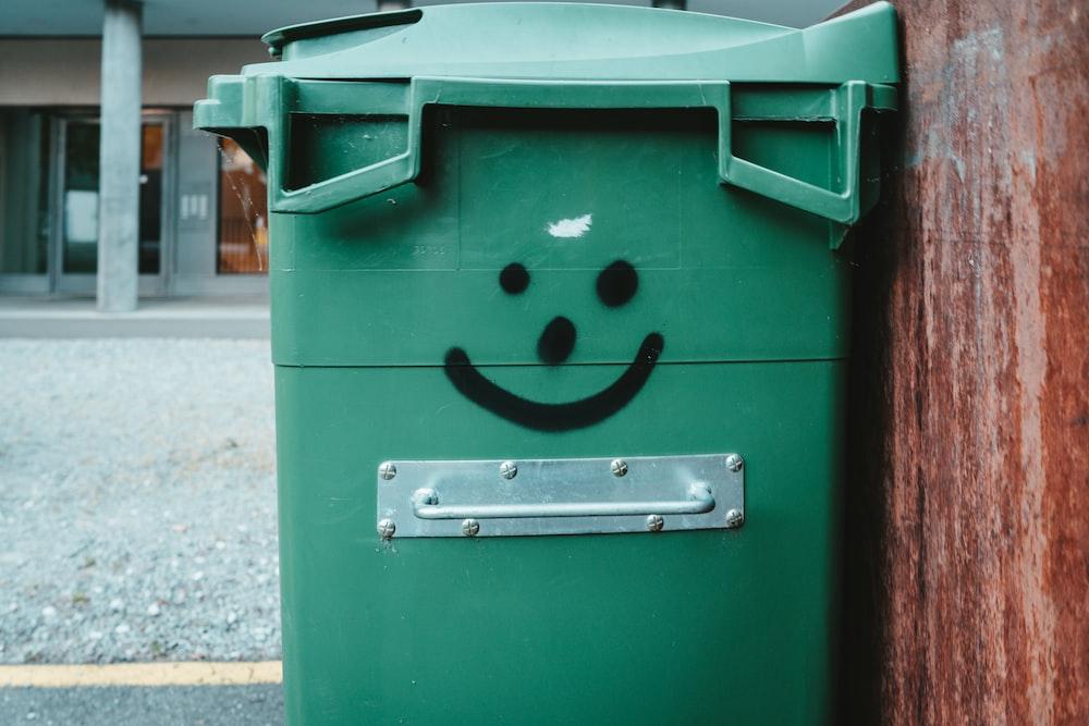 green trash bin on sidewalk