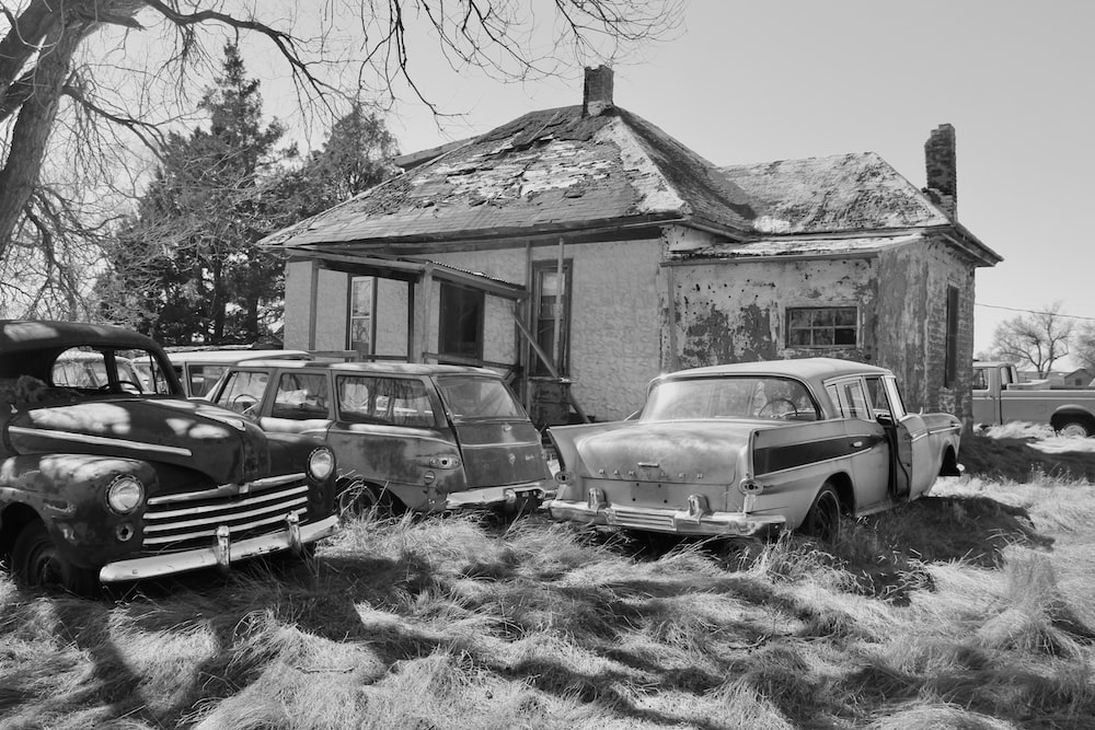 grayscale photo of 2 cars parked beside house