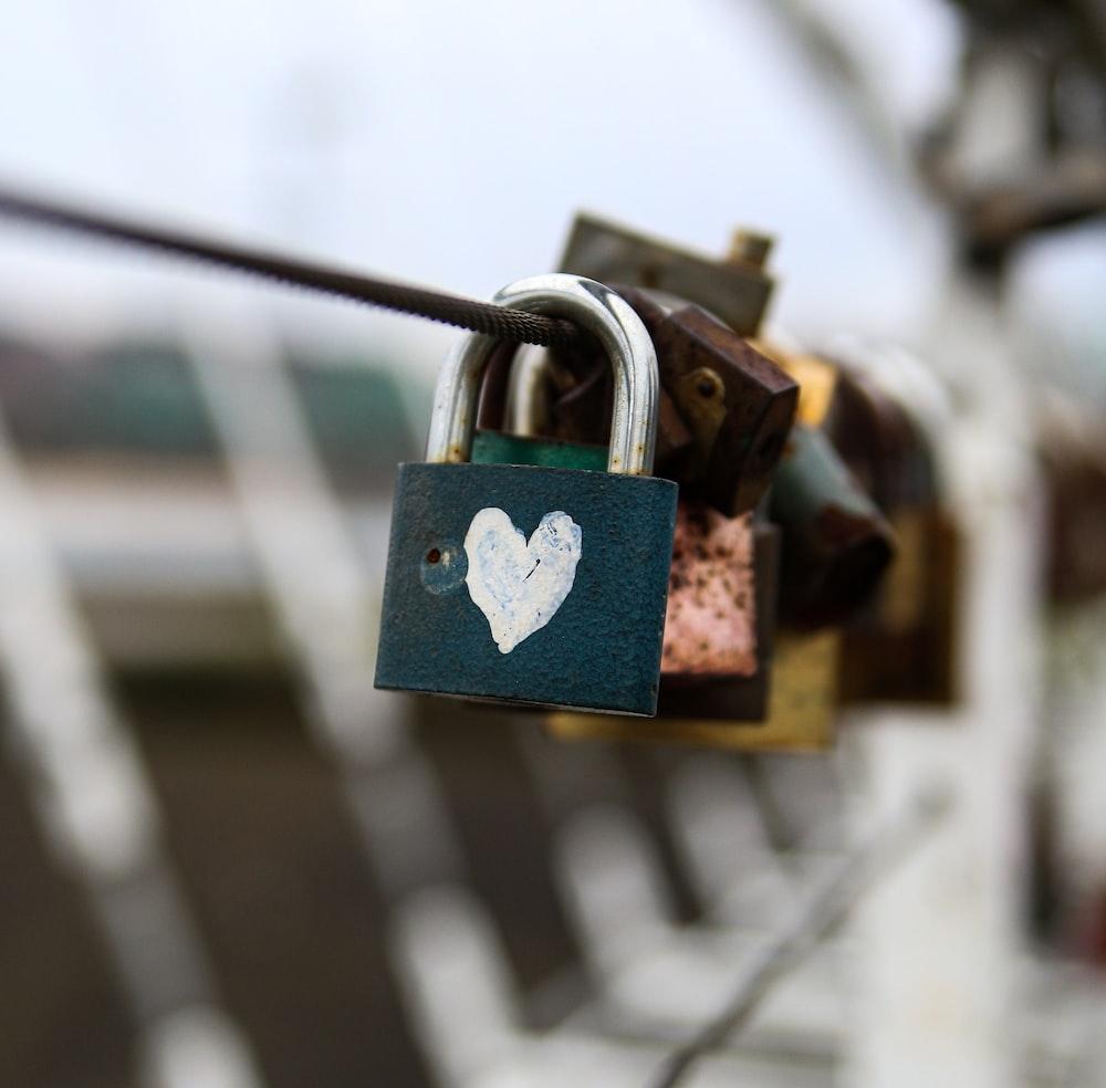 brass padlock on grey metal fence
