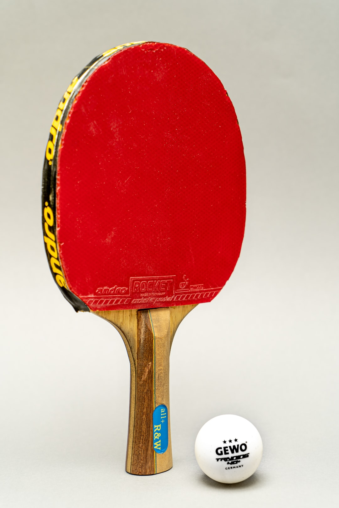 A ping-pong racket with a ball in front of a backdrop!