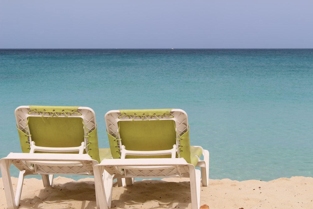 2 white and blue beach chairs on beach shore during daytime
