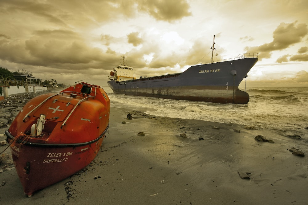red and black ship on beach during daytime