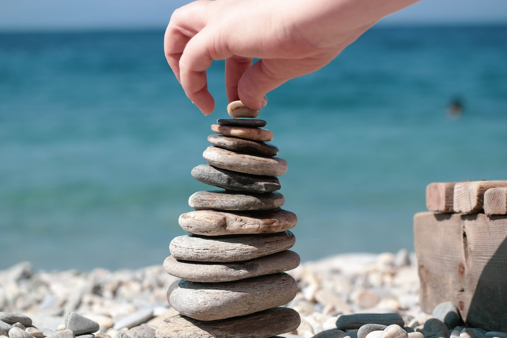 person holding stack of stones
