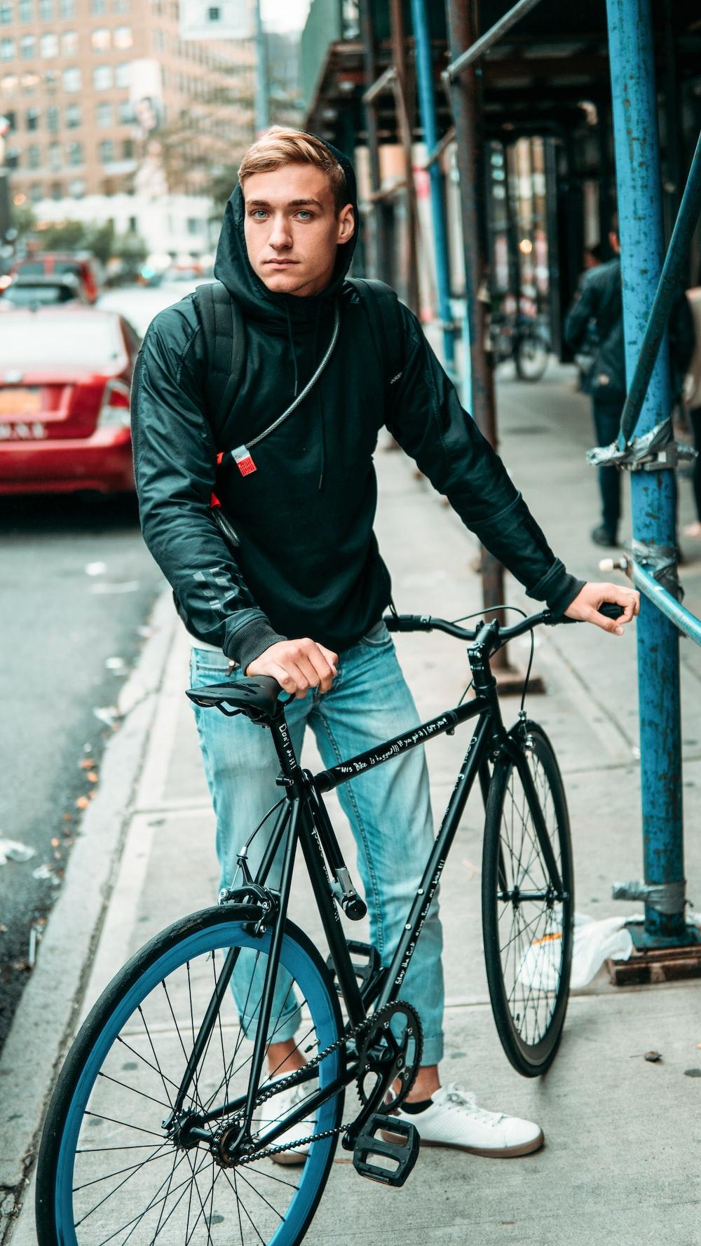 man in black hoodie and blue denim jeans riding on black bicycle